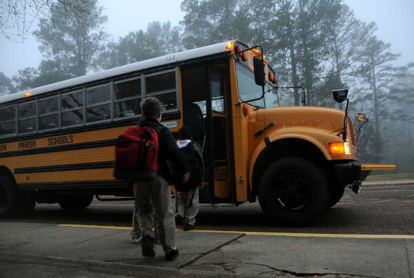 Kids being picked up for school by a bus on a foggy day