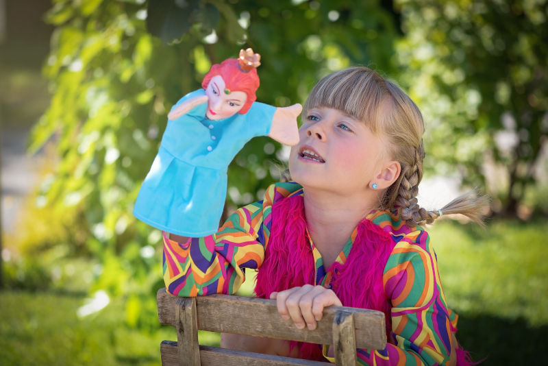 A blond girl plays with a puppet outdoors